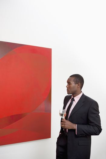 Young man looking at wall painting in art gallery