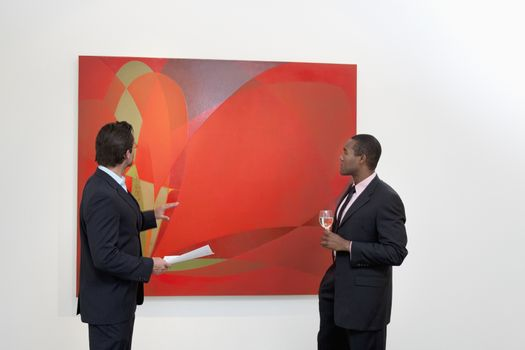 Two males talking over painting in art gallery