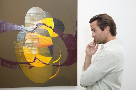Thoughtful man looking at wall painting in art gallery