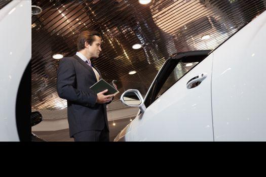 Salesman standing in automobile showroom