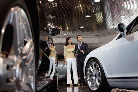 Woman standing with auto salesman in car showroom