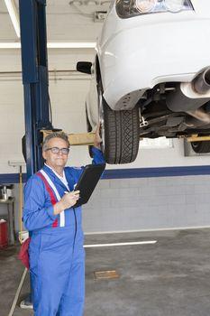 Portrait of senior mechanic with tablet PC