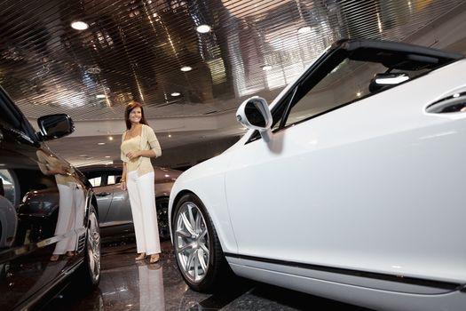 Full-length of smiling woman standing in car showroom