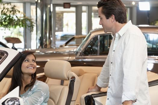 Couple checking out new cars in dealership showroom