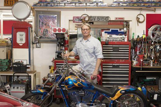 Senior man standing behind motorcycle in automobile repair shop