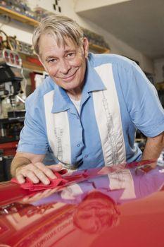 Smiling elderly man cleaning red hood of car in automobile repair shop