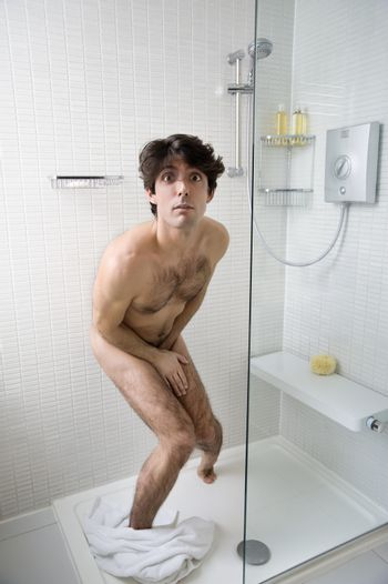 Scared naked man in bathroom