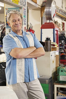 Portrait of smiling elderly man in automobile workshop