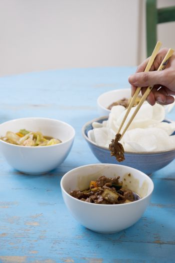 Close of human hand with chopsticks holding food