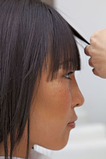 Side view of Asian woman getting a new haircut