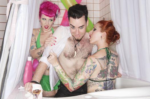 Erotic tattooed women seducing man in the bathtub