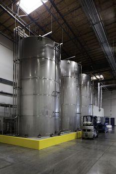 Huge silos and a forklift at bottling plant
