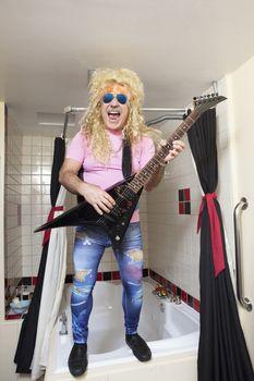 Full-length of guitarist playing guitar in bathroom
