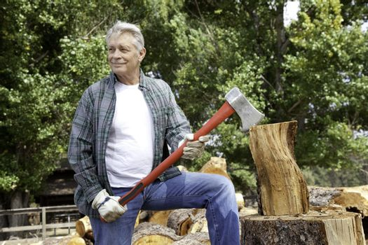 Senior lumber jack holding an axe and looking away