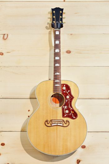 Acoustic guitar with label on a wood grain wall