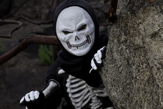 Boy dressed as skeleton creeping out