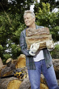 Senior man carrying firewood logs