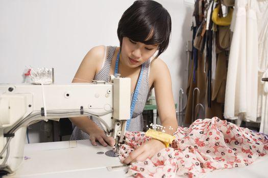 Fashion designer sewing fabric
