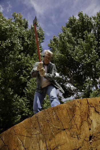Low angle view of man about to chop wood