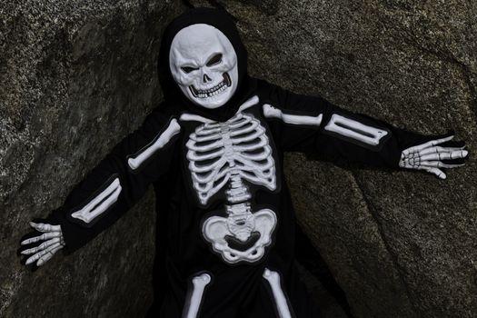 Boy dressed up as skeleton posing on rock