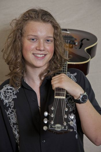 Portrait of smiling young musician with guitar