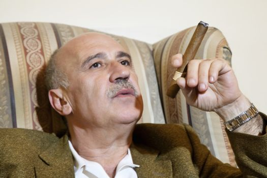 Mature man smoking cigar while relaxing on armchair