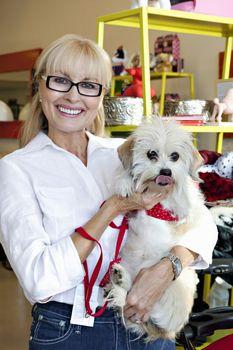 Portrait of pet shop owner carrying dog