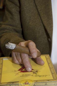 Cropped image of hands holding burning cigar