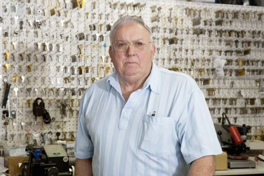 Portrait of a senior male owner of key store