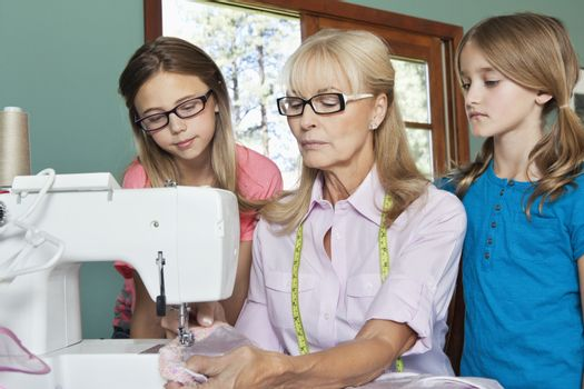 Granddaughters looking at grandmother sewing cloth