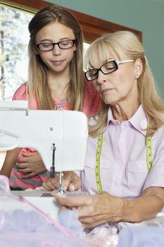 Granddaughter looking at grandmother sewing cloth
