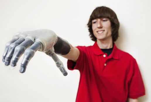 Young man looking at his prosthetic hand over gray background