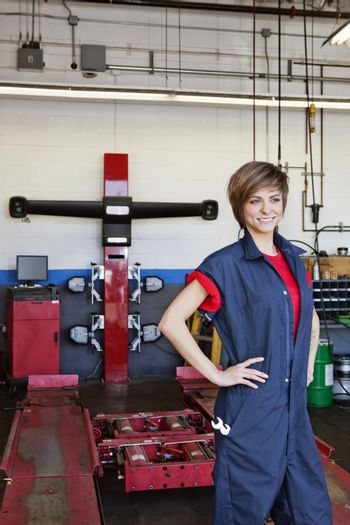 Happy young female mechanic with hands on hips in automobile repair shop