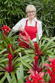 Portrait of a happy woman watering plants in botanical garden