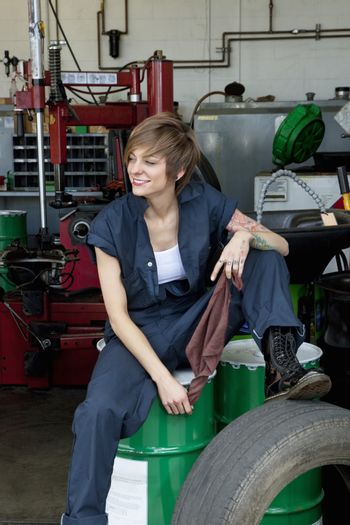 Happy young female mechanic sitting on oil drum in automobile repair shop