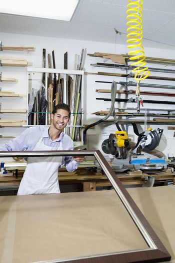 Portrait of a happy craftsman working at picture frame