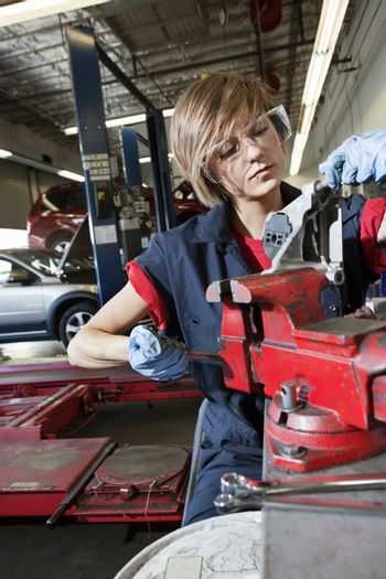 Young mechanic in protective clothing concentrating on repairing machine part in garage