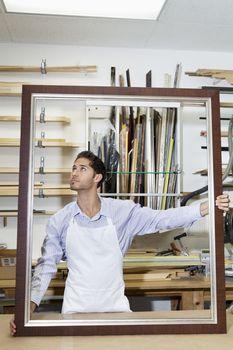Young craftsman looking on frame's corner in workshop