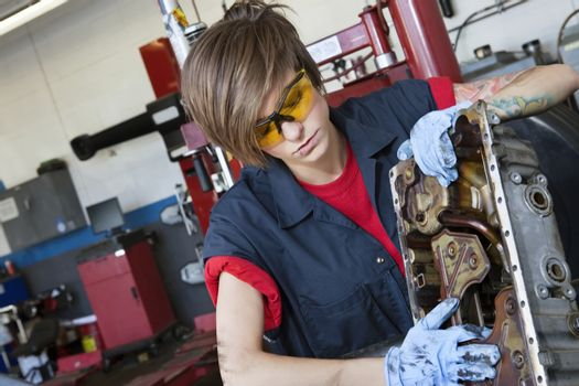 Young female mechanic working on automobile machinery part in workshop
