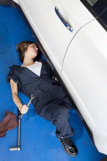 Woman lying down on floor working on car in automobile garage