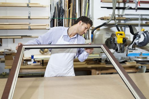 Young craftsman looking at picture frame