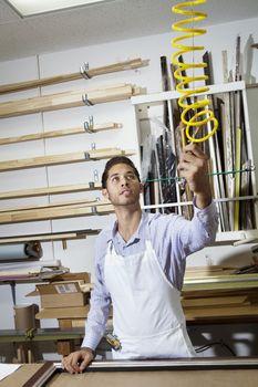 Young craftsman holding equipment in frame workshop