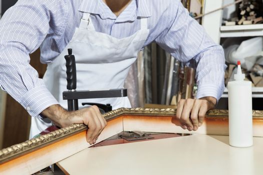 Midsection of a young craftsman working on picture frame's corner