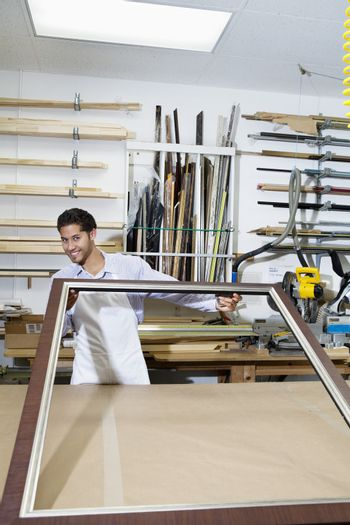 Portrait of a happy craftsman working on picture frame in workshop