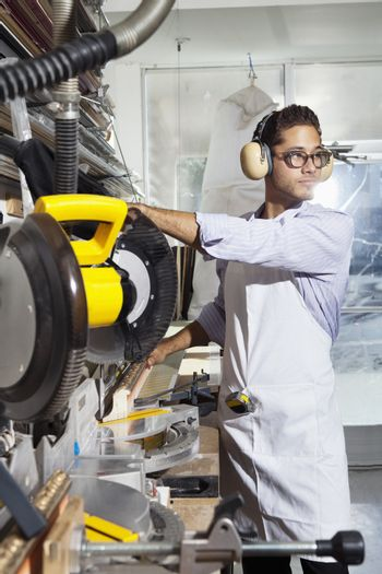 Young craftsman wearing protective gear while using circular saw