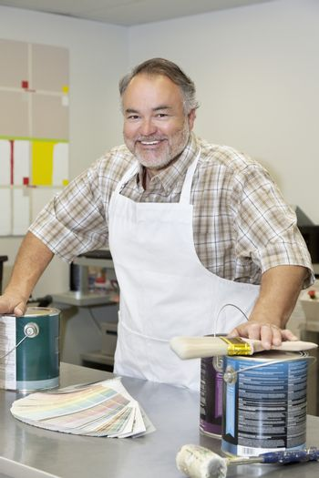 Portrait of a cheerful mature store clerk with paint cans and brush in hardware shop
