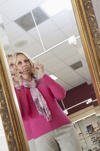 Reflection of senior woman trying on glasses