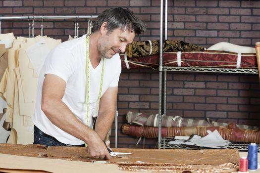Mature male dressmaker cutting fabric in design studio