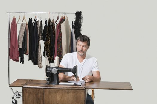 Mature male dressmaker sitting at sewing machine over colored background