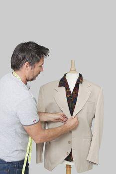 Male dressmaker adjusting suit on tailor's dummy over colored background